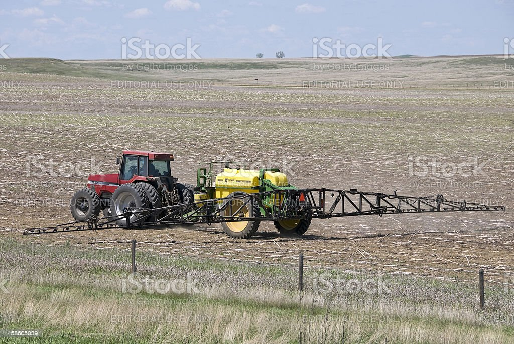 Tractor pulling sprayer over corn field royalty-free stock photo