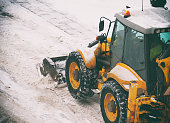 Tractor shoveling snow on the street.