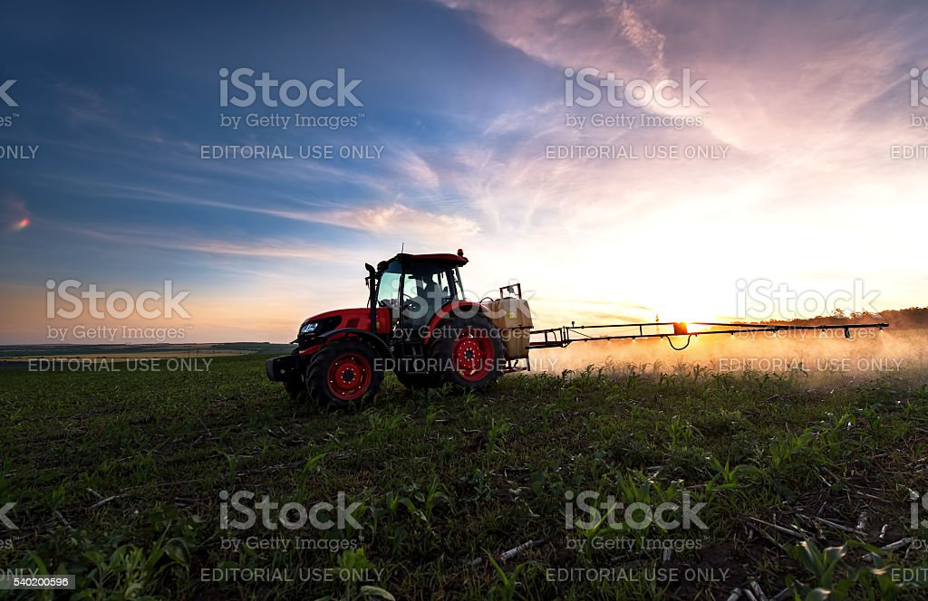 Tractor spraying a field on farm in spring, agriculture stock photo