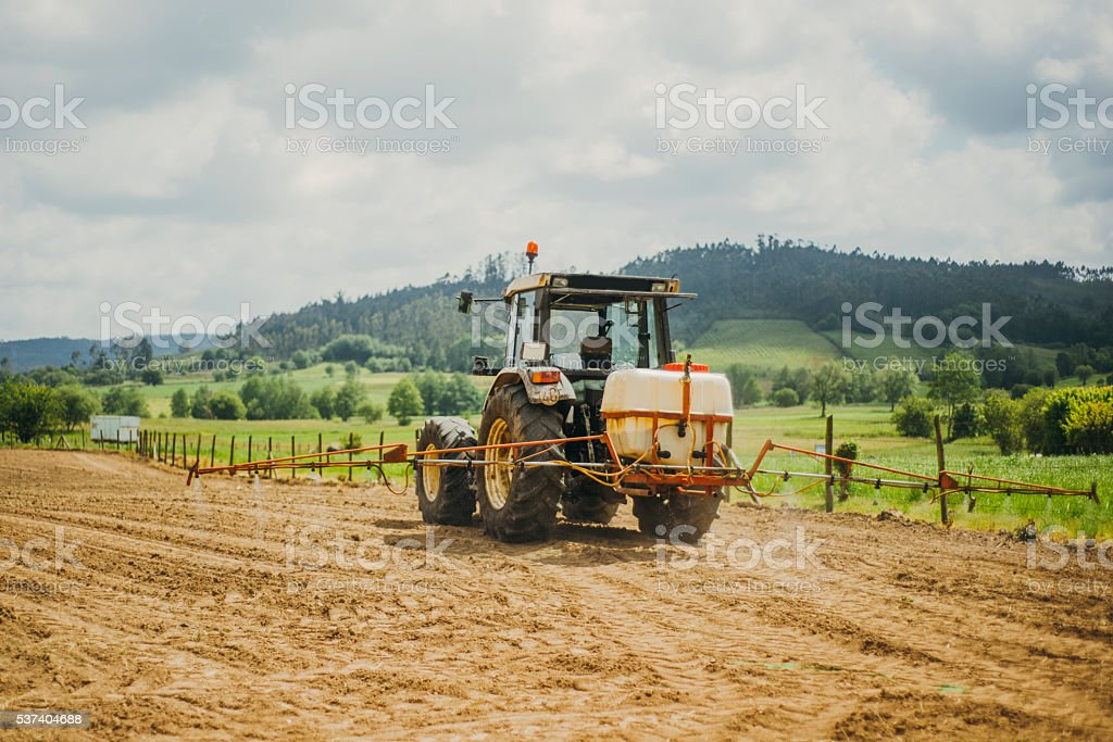 Tractor spraying fertilizer stock photo