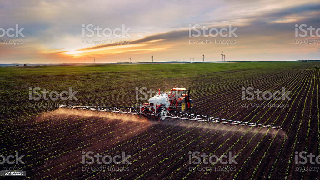 Tractor spraying field at spring stock photo