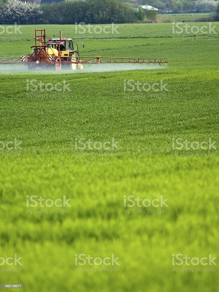 A tractor spraying water into an open field royalty-free stock photo