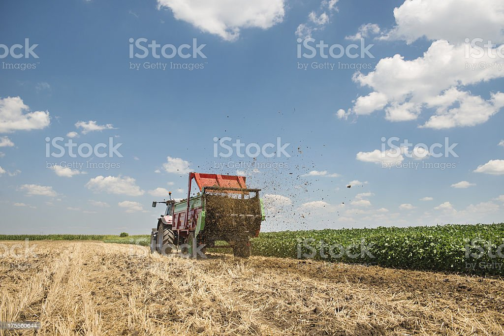 A tractor spreading manure on a field stock photo