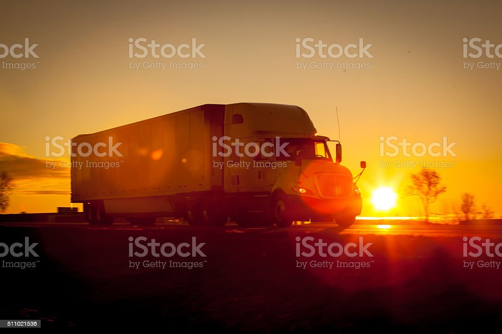 Tractor trailer driving down the highway at sunrise. stock photo