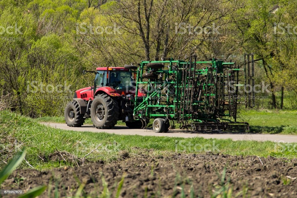 Tractor with cultivator on the rural road stock photo