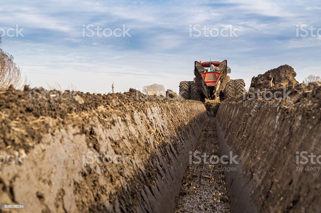 Tractor with double wheeled ditcher digging drainage canal. stock photo