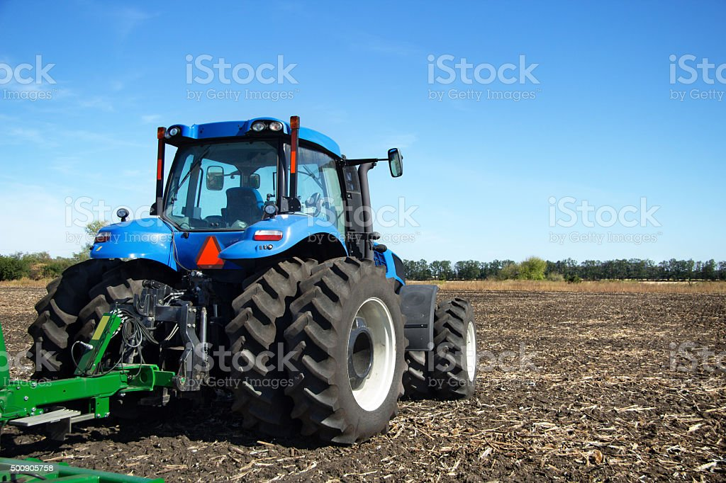 Tractor with plow working in the field stock photo