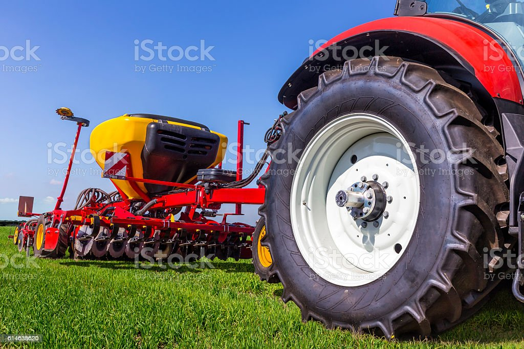 Tractor with seeding and plowing machine on the plantation stock photo