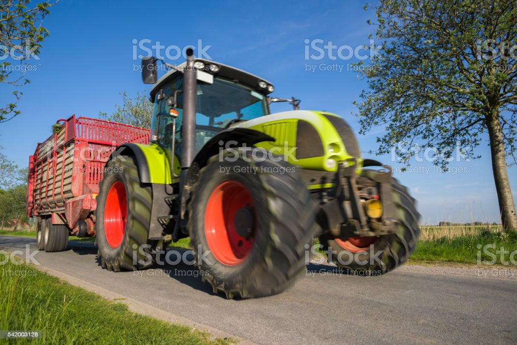 Tractor with trailer on road under clear sky stock photo