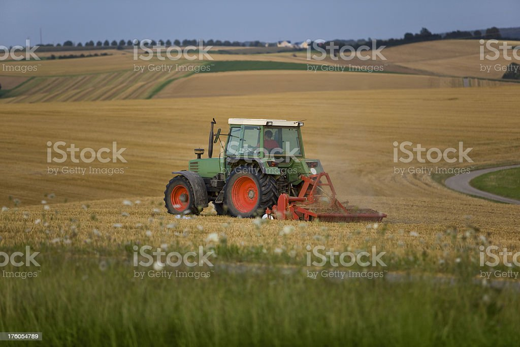 Tractor working on an empty field royalty-free stock photo