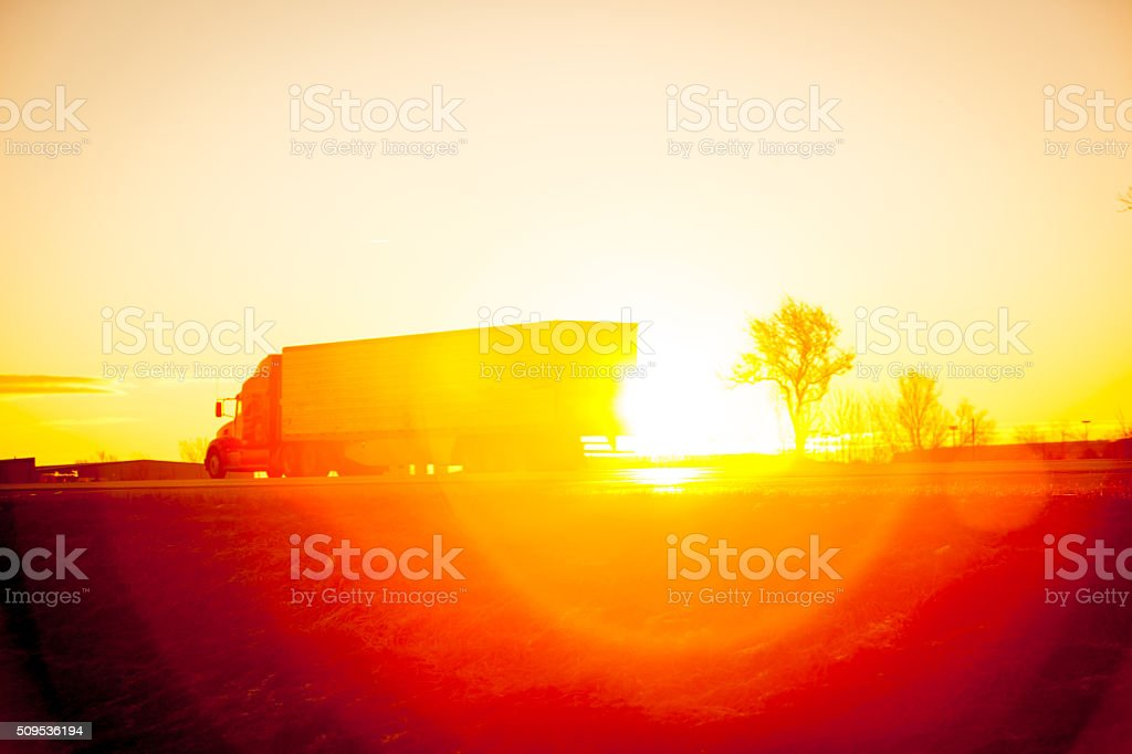 Tractore trailer driving down the highway at sunrise. stock photo