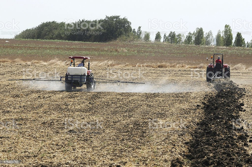 Tractors Plowing and Spraying Field royalty-free stock photo