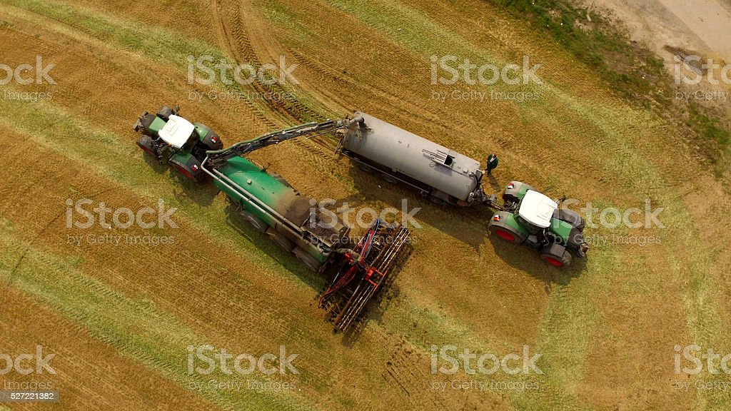 Tractors with Liquid Manure Spreader on field - Aerial view stock photo