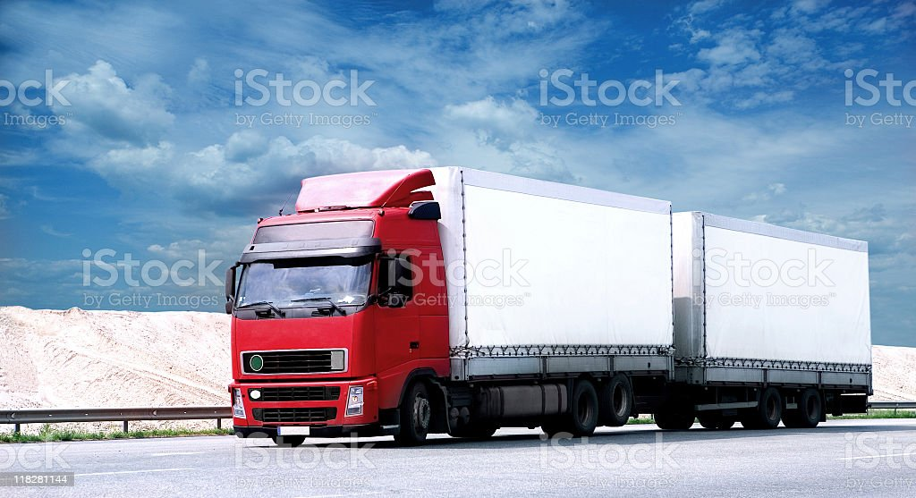A tractor-trailer hauling two trailers along the highway royalty-free stock photo