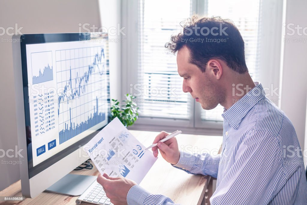 Trader analyzing financial report and trading charts and computer screen stock photo
