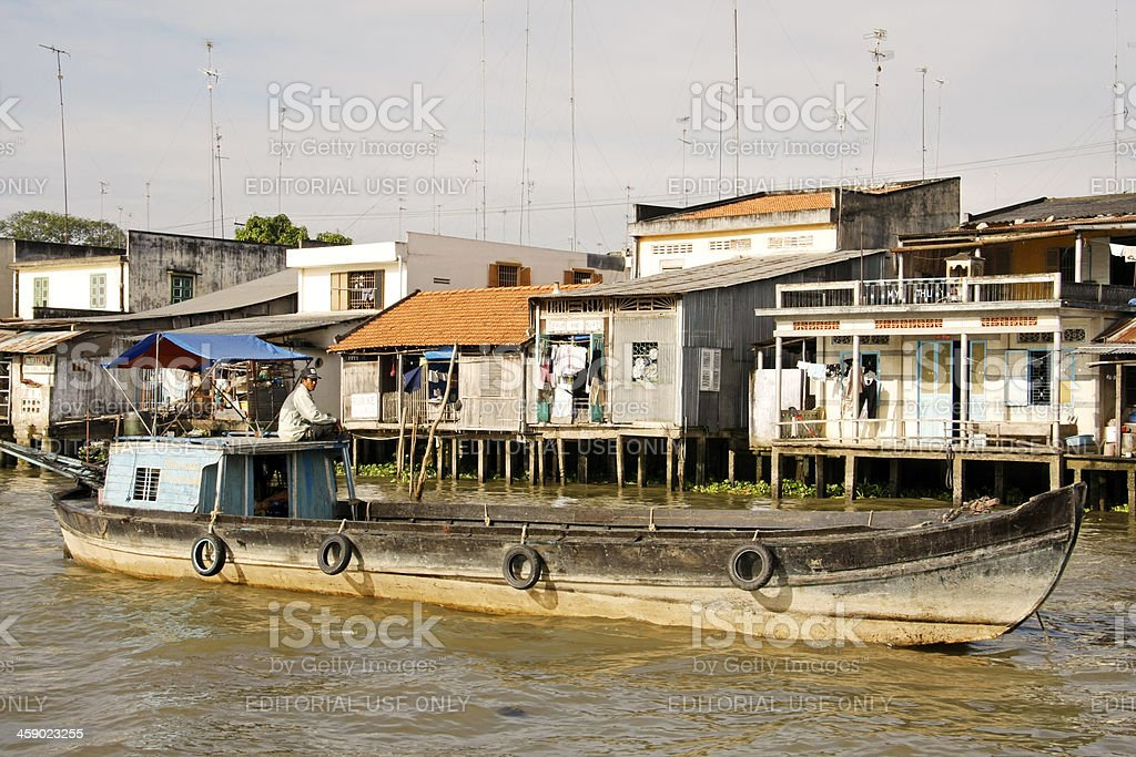 Trader on empty long boat in Viet Nam royalty-free stock photo
