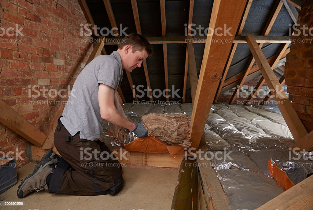Tradesman fits insulation in attic stock photo