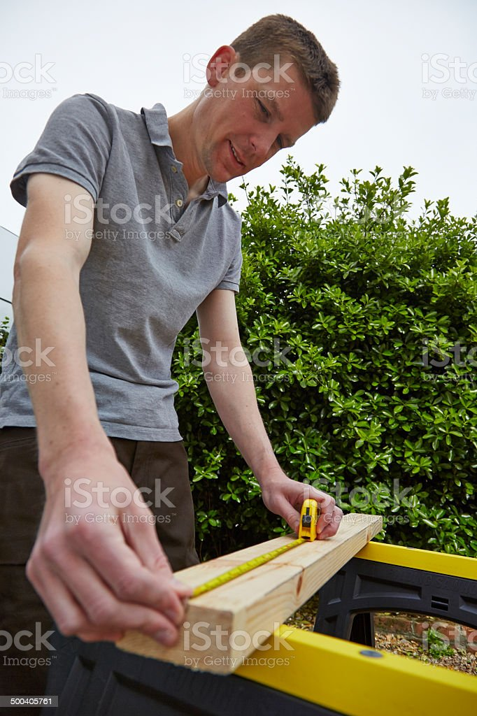 Tradesman measures a piece of timber royalty-free stock photo