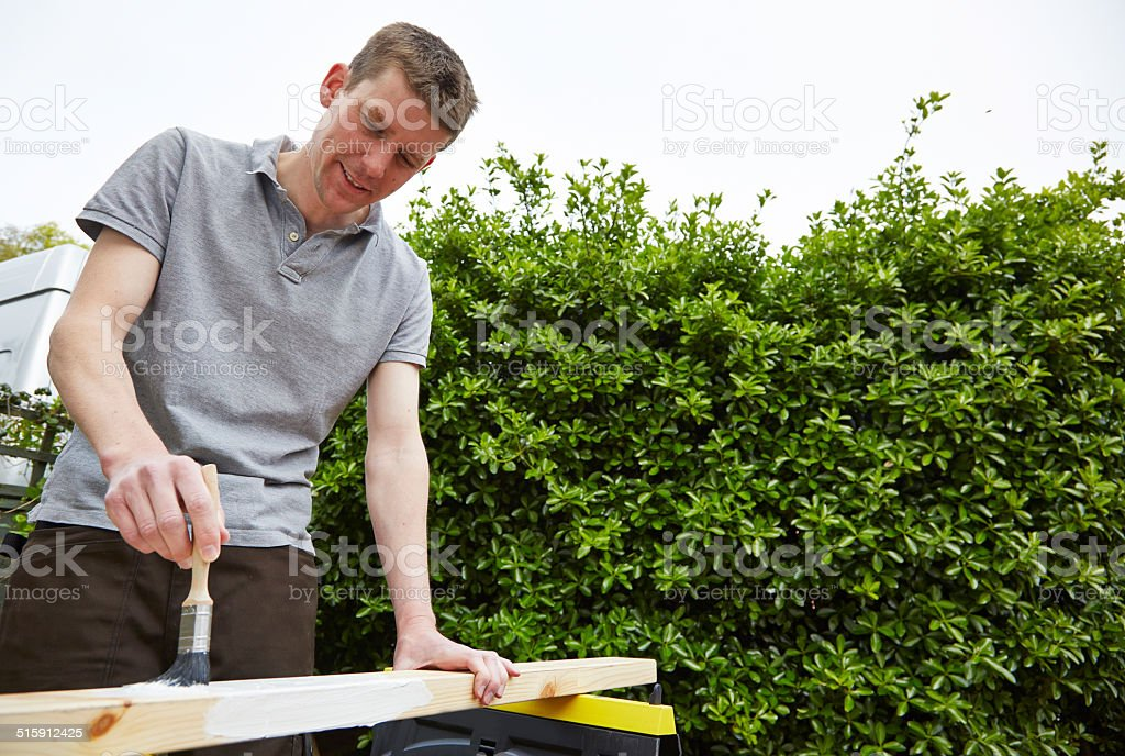Tradesman paints a length of wood stock photo