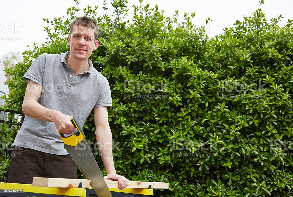 Tradesman sawing a piece of timber royalty-free stock photo