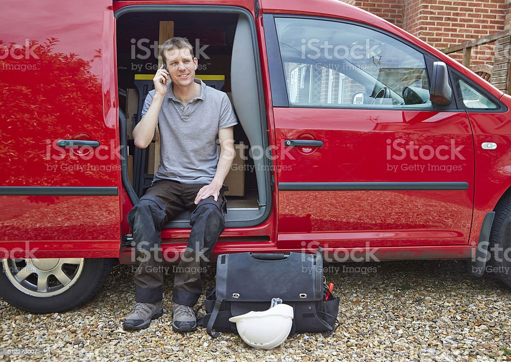 Tradesman sitting in van talking on cell phone stock photo