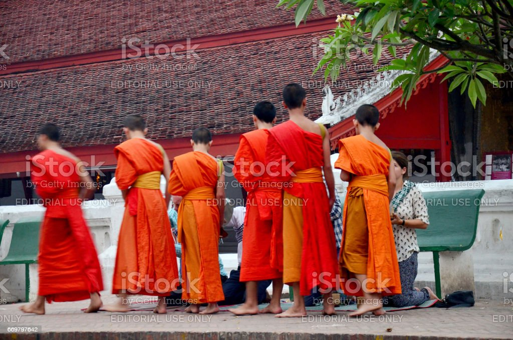 Tradition of almsgiving with sticky rice by Monks procession walk on the road stock photo