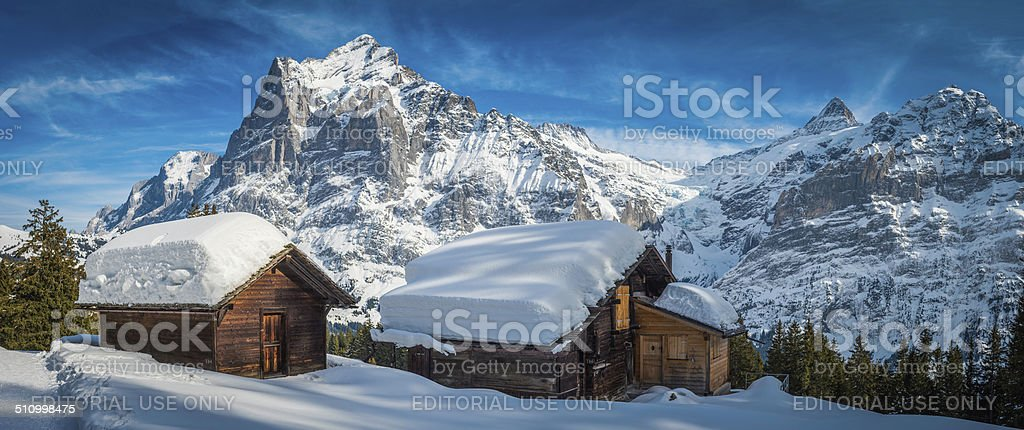 Traditional Alpine chalets in idyllic snowy winter mountains panorama Switzerland stock photo