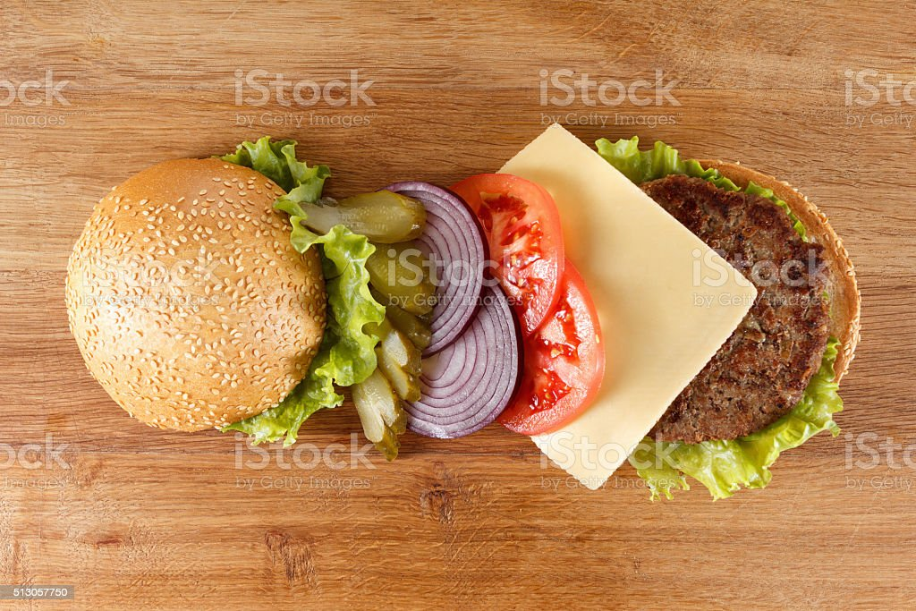 Traditional American cheeseburger. Meat, bun and vegetables close up stock photo