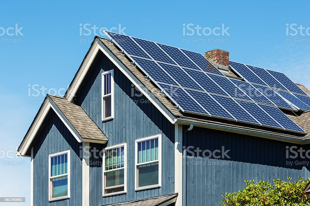 Traditional American Home with Modern Solar Panels on Roof stock photo