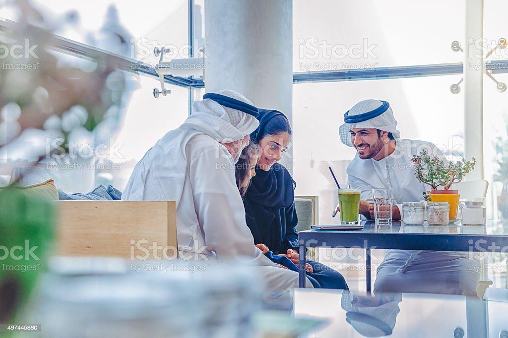 Traditional Arab family enjoying at cafe stock photo