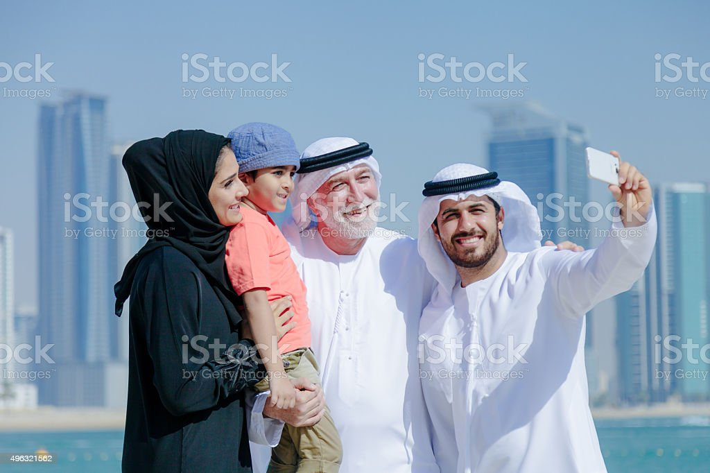 Traditional Arabian family taking selfie at park stock photo