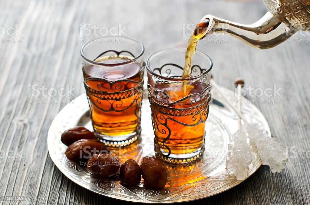Traditional arabic tea with dates and sugar on a plate stock photo