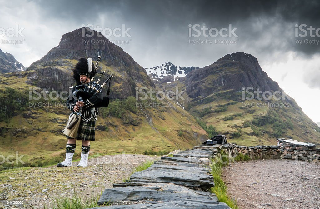 Traditional bagpiper in the scottish highlands by Glencoe stock photo
