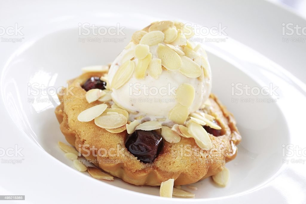 traditional bakewell tart with ice cream and almonds stock photo