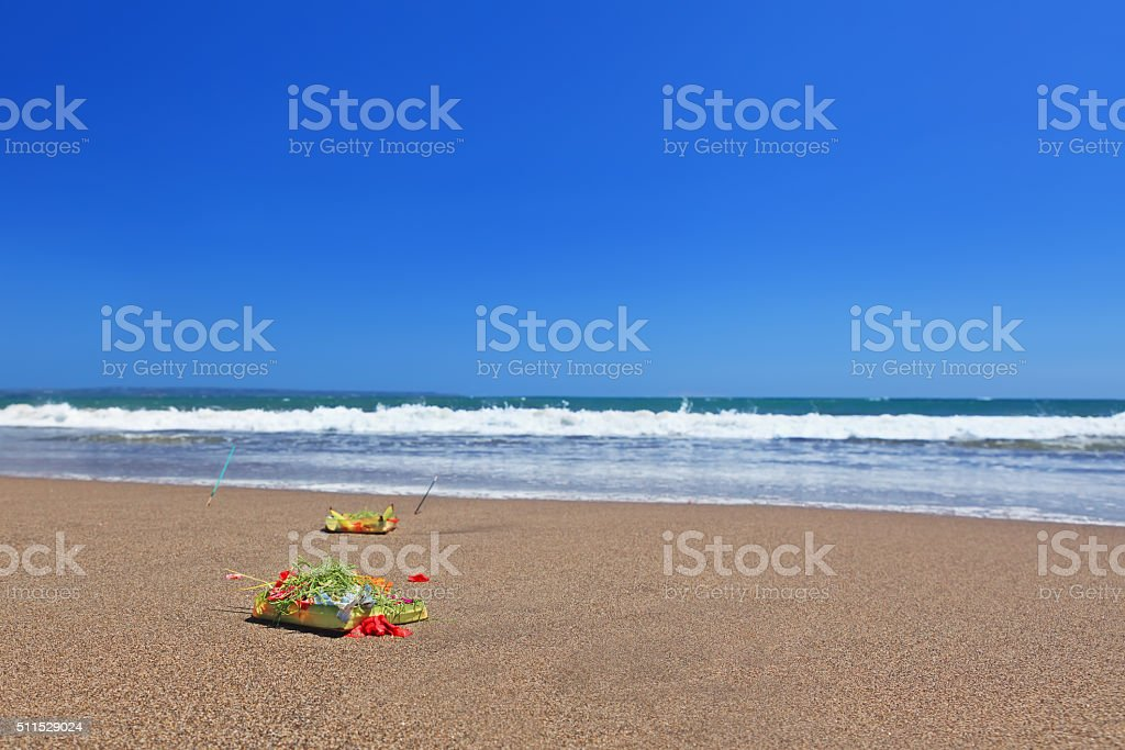 Traditional Balinese ceremonial offering Canang sari on ocean beach stock photo