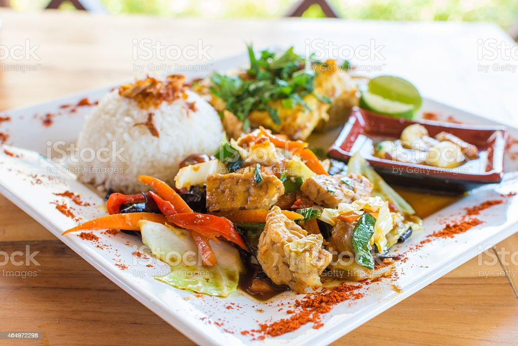 Traditional Balinese cuisine. Vegetable and chicken stir-fry with rice. stock photo
