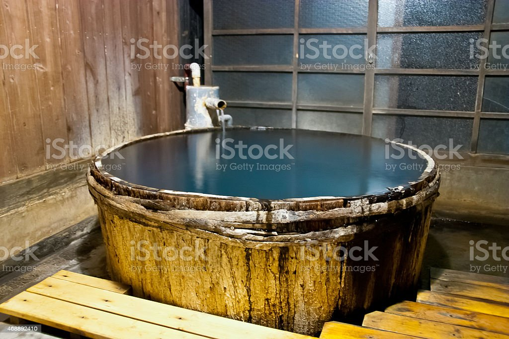 Traditional bath tub filled with thermal water - Japan stock photo