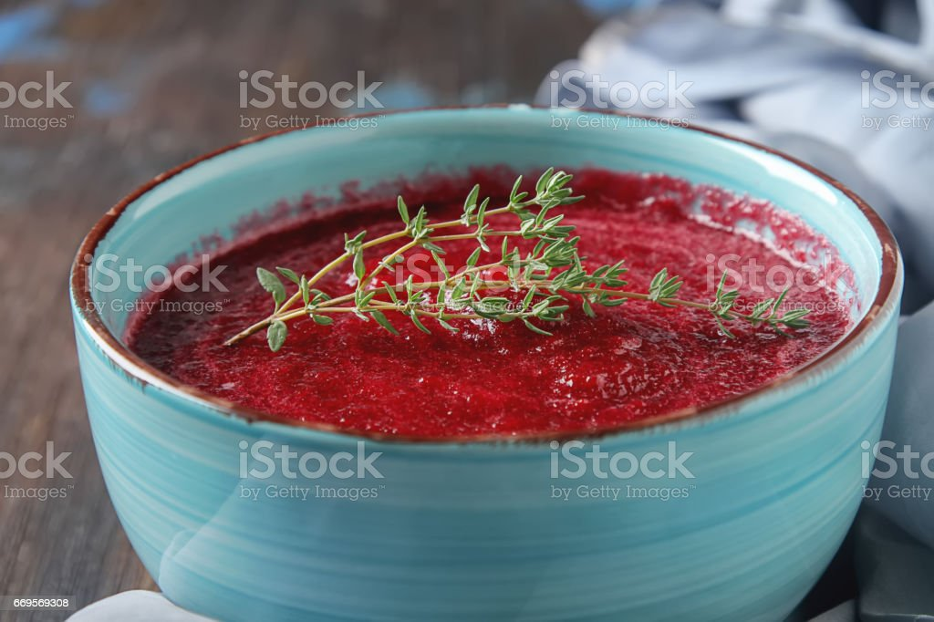 Traditional beetroot soup in a blue plate with Temyan. Dark wood background. Light fabric. free space text. stock photo