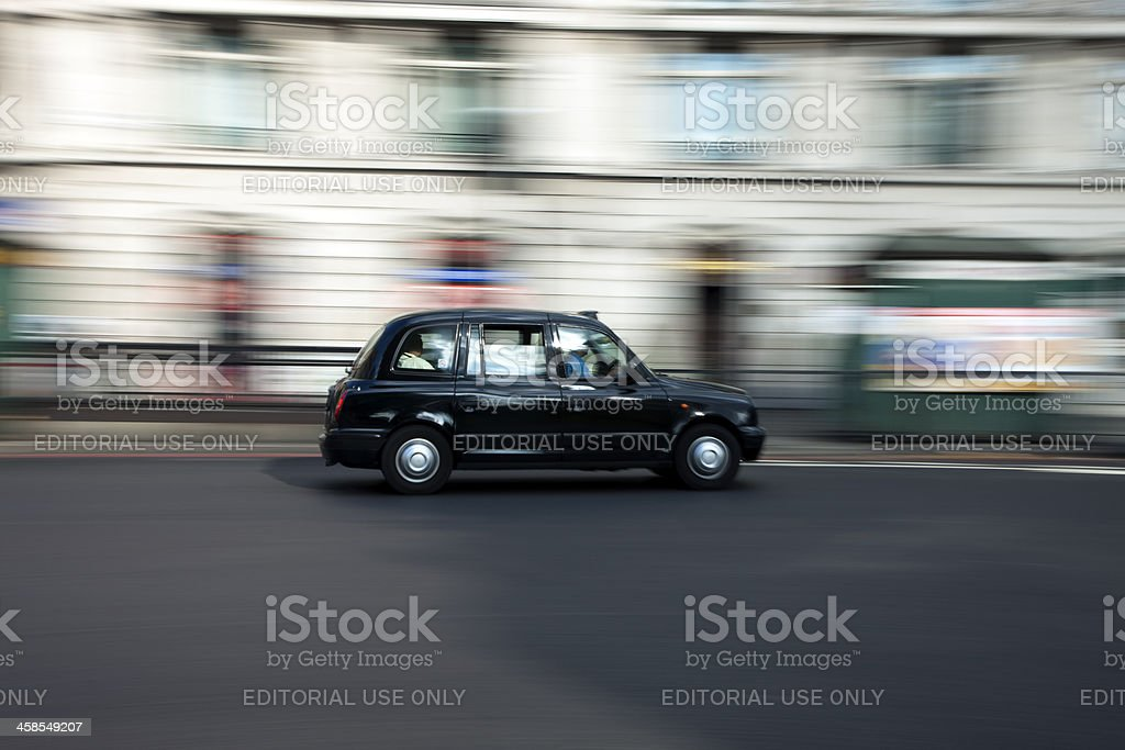 Traditional Black Taxi Cab Speeding Down Street in London royalty-free stock photo