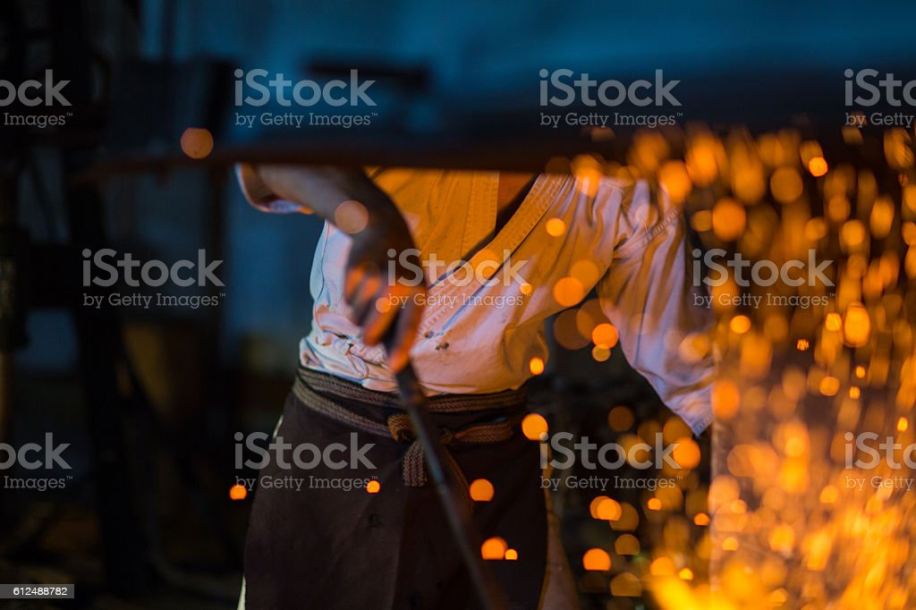 Traditional blacksmith stokes a fire preparing to forge a sword stock photo