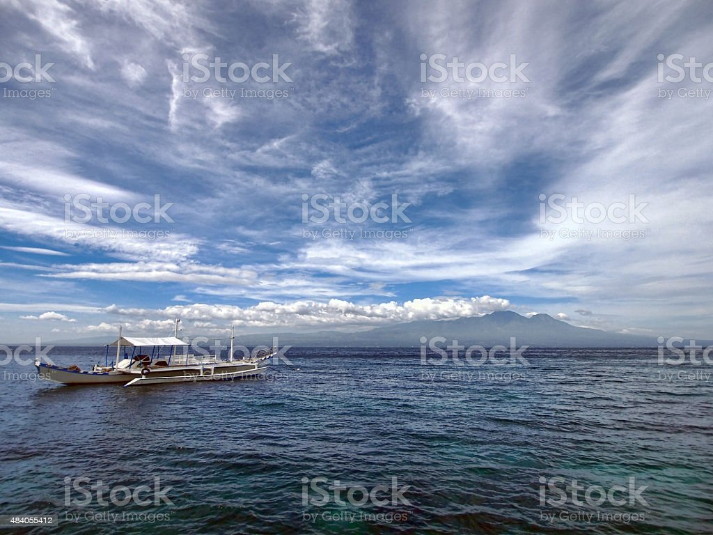 Traditional boat, ocean, mountain and blue sky stock photo