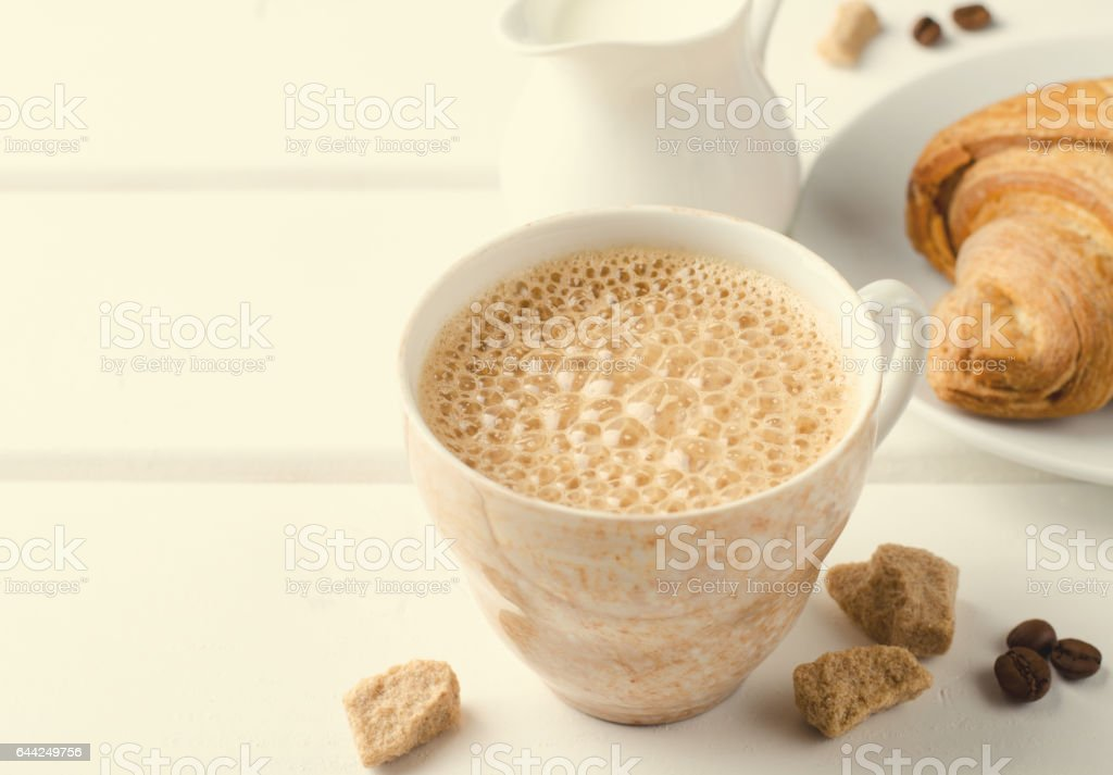 Traditional breakfast with fresh croissants and coffee on white wooden background. stock photo