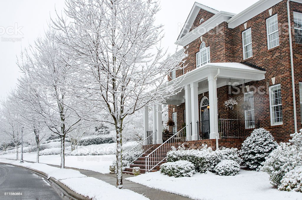 Traditional Brick Home During a Winter Snow Storm stock photo