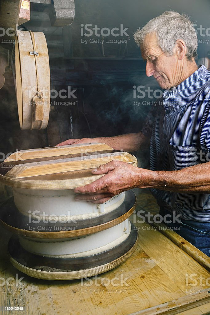 Traditional cheese maker places weight on fresh wheels stock photo