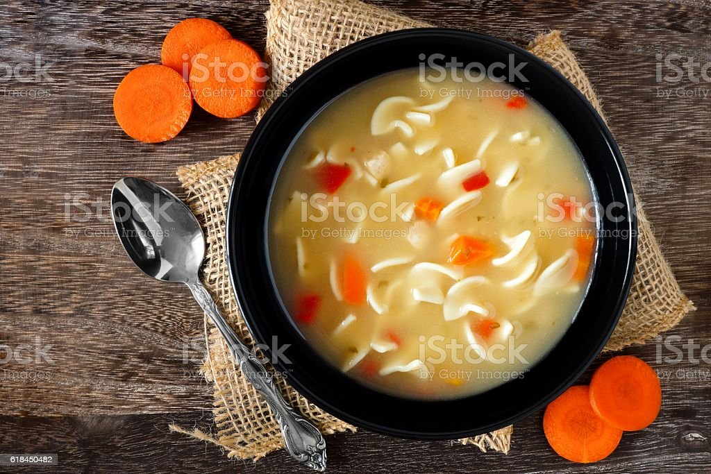 Traditional chicken noodle soup, overhead scene on rustic wood stock photo
