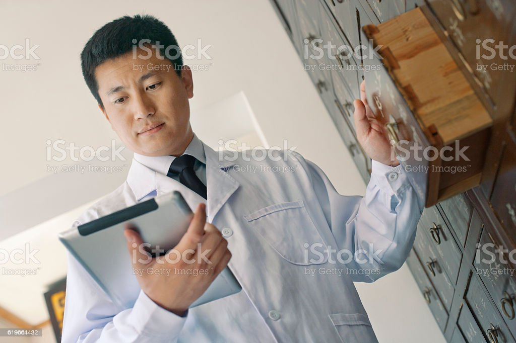 Traditional Chinese doctor looking at tablet computer stock photo