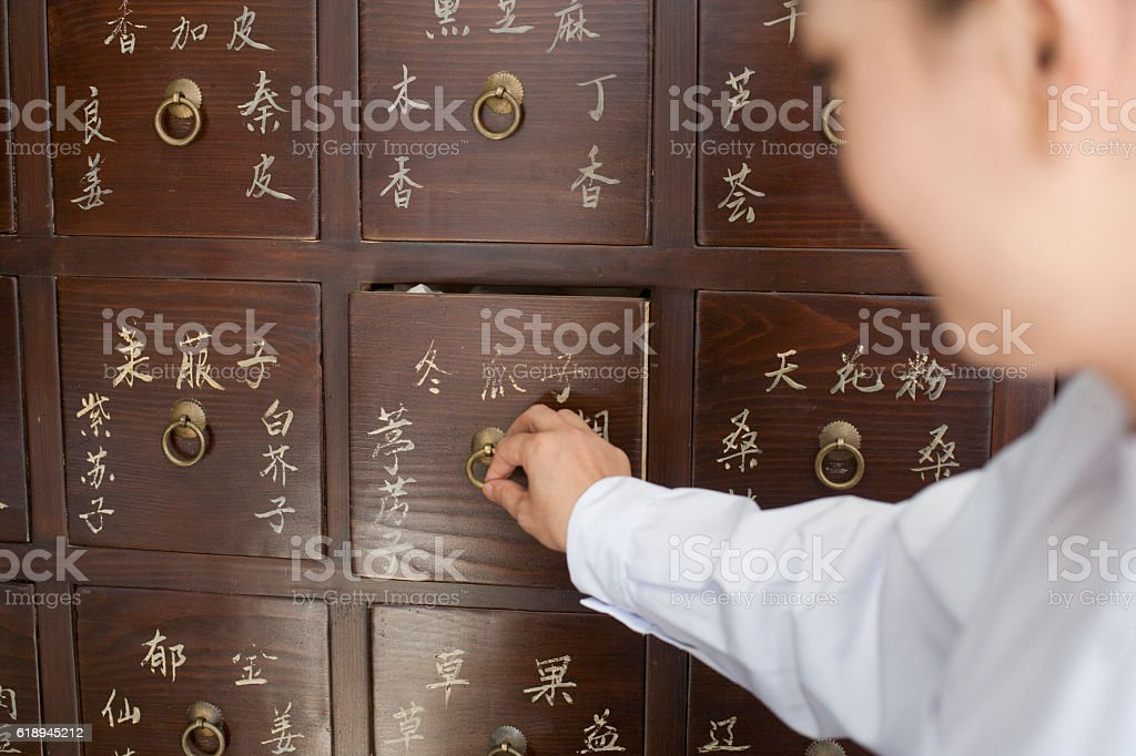 Traditional Chinese doctor opening medicine cabinet drawer stock photo