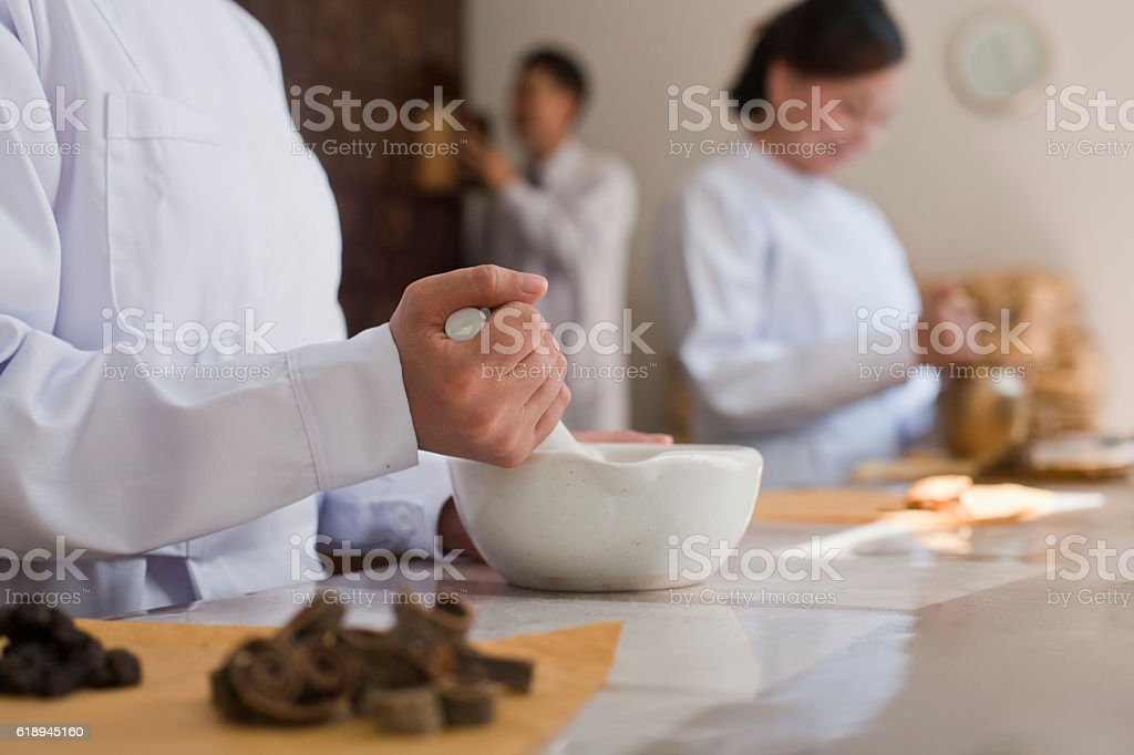 Traditional Chinese doctors mixing medicine ingredients stock photo