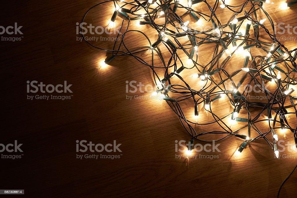 Traditional Christmas Tree lights lying on a wooden floor. stock photo