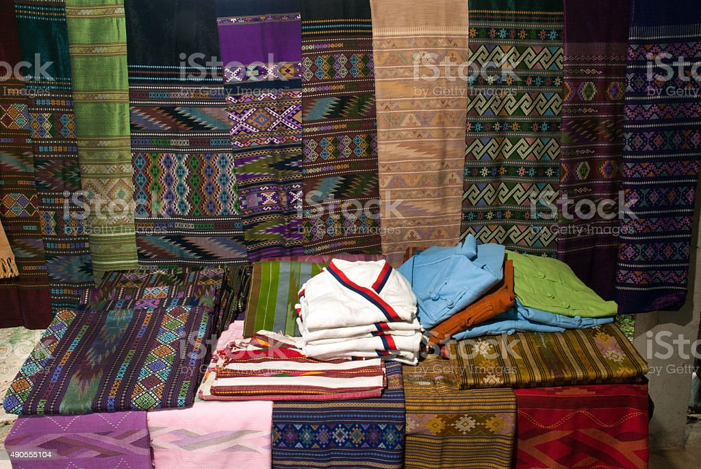 Traditional clothes Lua minority show on table and hanging. stock photo